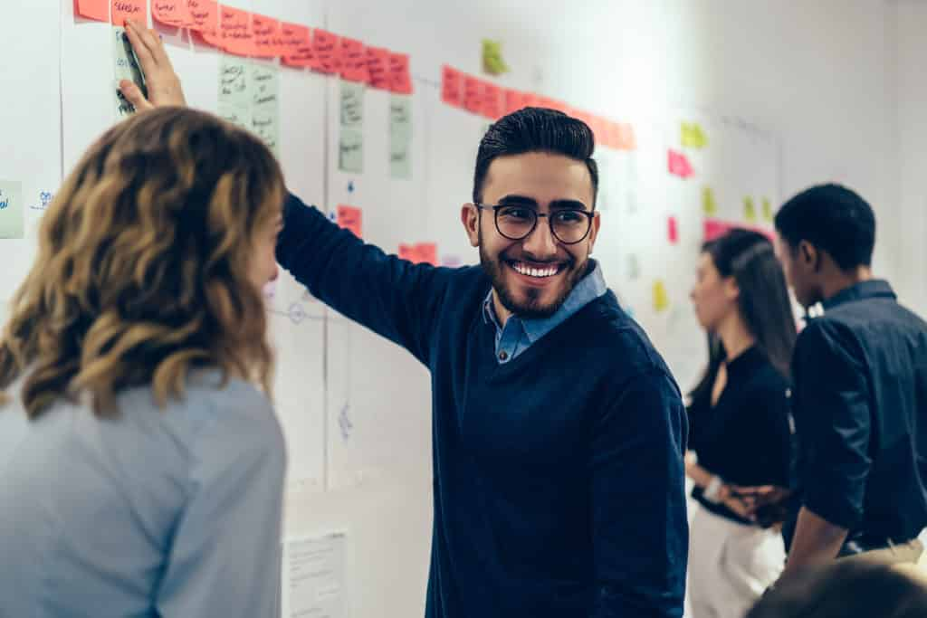 Positive young man smiling while collaborating with colleagues on presentation